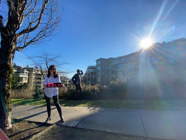Two real estate agents standing in front of a sold condo in Coquitlam
