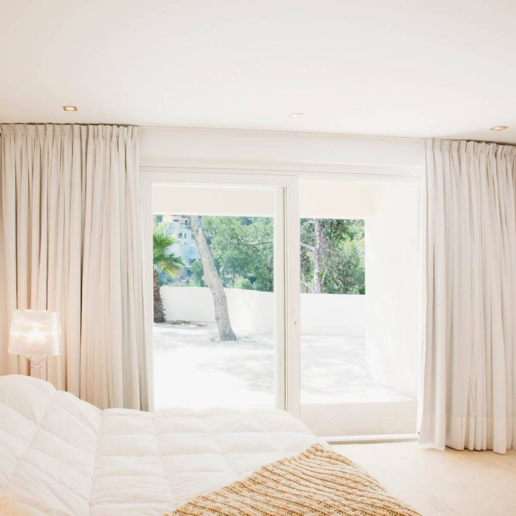 sunny bedroom with curtains on large windows